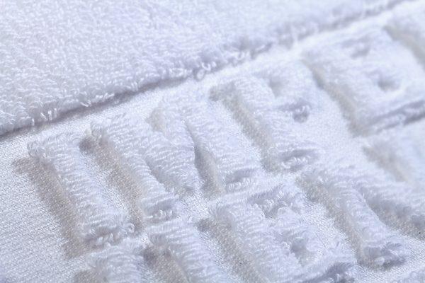 Handtuch Hoch Tief Relief Einwebung terry towel inweaving cotton Baumwolle Detail Buchstaben Hotel Imperial weiss